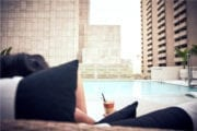 Person holding a cocktail in foreground, in front of pool, buildings in the background
