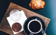 Overhead view of board with of coffee cup, cookie and croissant next to board